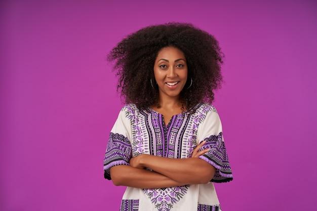 Innenporträt der positiven jungen dunkelhäutigen frau mit dem lockigen haar, das weiß gemustertes hemd trägt, mit gefalteten händen auf purpur aufwirft und fröhlich lächelt