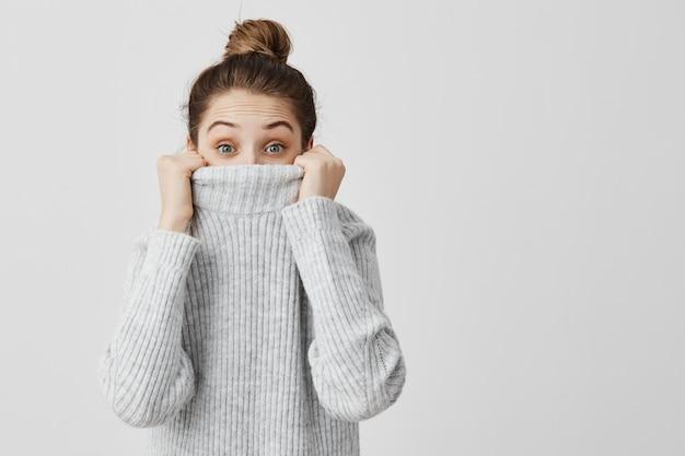 Innenporträt der reizenden frau, die aus ihrem pullover herausschaut, amüsant. lächerlicher weiblicher blick von unten von kleidungsmädchen will nicht gefunden werden. körpersprache