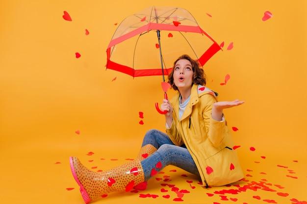 Innenporträt der schockierten schönen frau, die herzregen betrachtet. studioaufnahme des fröhlichen mädchens mit regenschirm lokalisiert auf heller wand am valentinstag.