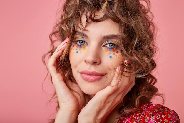 Innenporträt der schönen dame mit hellbraunem lockigem haar, romantisch schauend, ihr gesicht mit den händen berührend, isoliert