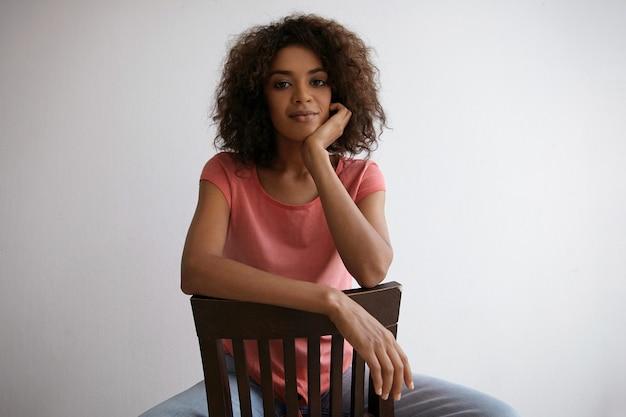 Innenporträt der schönen dunkelhäutigen frau mit dem braunen lockigen haar, das auf stuhl sitzt, mit ruhigem gesicht und hellem lächeln schauend sieht, handfläche unter ihrem kinn hält