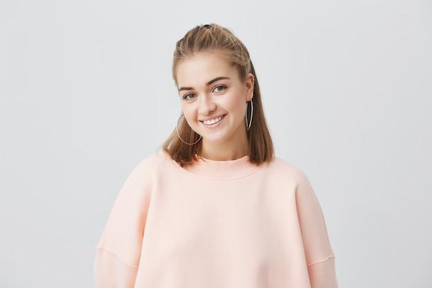 Innenporträt der schönen jungen kaukasischen frau mit dem glatten blonden haar, das fröhlich lächelt und ihre weißen zähne zur kamera zeigt, während sie sich an ihren freien tagen glücklich und sorglos fühlen