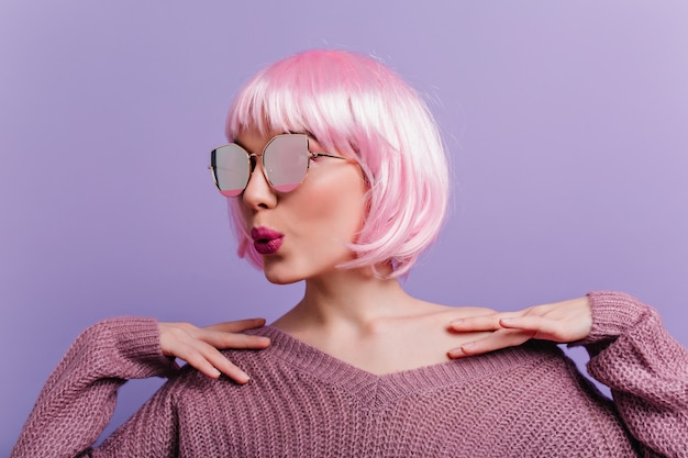 Innenporträt der siegreichen dame in den funkelnden gläsern und im gestrickten pullover, die auf lila wand stehen. foto des glamourösen mädchens in der rosa perücke, die mit küssendem gesichtsausdruck aufwirft.