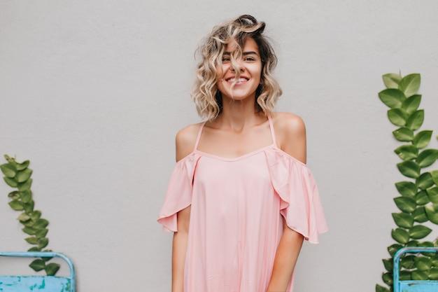 Innenporträt der sorglosen kurzhaarigen dame mit gebräunter haut. lächelndes gewinnendes mädchen in der rosa kleidung, die mit grünen pflanzen aufwirft.