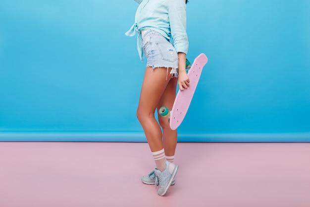 Innenporträt der sportlichen jungen frau mit bronzehaut, die neben hellblauer wand genießt. formschönes mädchen mit longboard trägt trendige schuhe und süße socken.