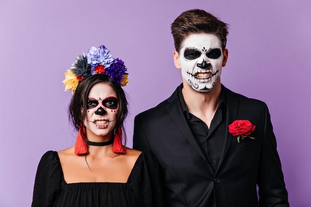 Innenporträt der verärgerten zombies lokalisiert auf lila hintergrund. lustiges emotionales paar in muertos-kostümen, die mit gruseligem gesichtsausdruck aufwerfen.
