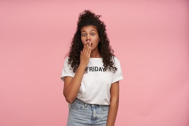 Innenporträt der verblüfften lockigen brünetten dunkelhäutigen frau, die ihren mund mit erhabener handfläche kegelt, während sie benommen aussieht und weißes t-shirt und blaue jeans auf rosa trägt