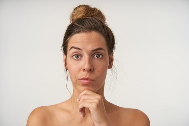 Innenporträt der verwirrten hübschen frau, die brötchenfrisur und kein make-up trägt und kinn mit hand mit hochgezogener augenbraue hält