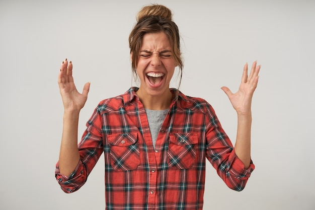 Innenporträt der wütenden jungen schönen frau, die mit erhobenen händen steht, heftig schreit, kariertes hemd und brötchenfrisur trägt