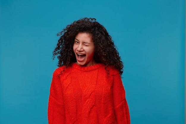 Innenporträt der zwinkernden glücklichen verspielten frau, die warmen übergroßen roten strickpullover trägt