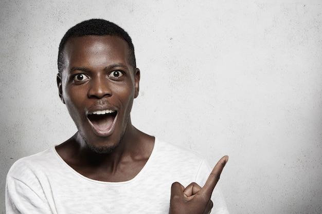 Innenporträt des afrikanischen mannes, der weißes t-shirt mit erstauntem und überraschtem blick trägt, mund weit öffnet und mit seinem zeigefinger auf leere wand anzeigt.