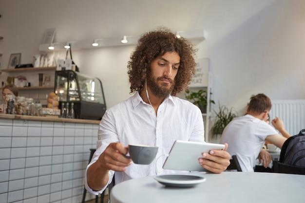 Innenporträt des attraktiven bärtigen lockigen kerls, der über caféinnenraum aufwirft, am tisch mit der tasse tee sitzt und aufmerksam auf bildschirm seines tabletts schaut