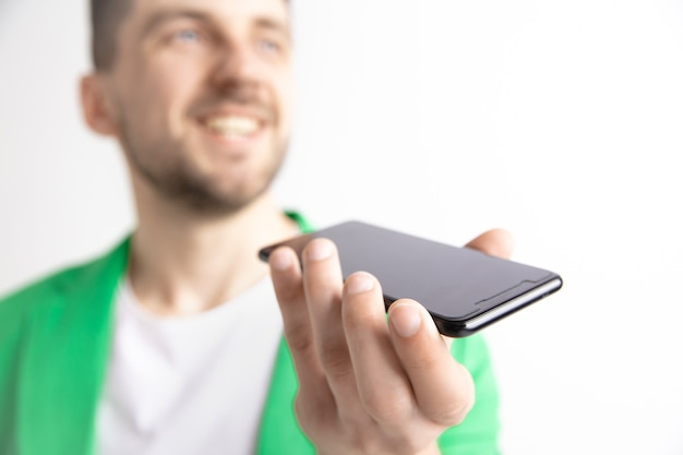 Innenporträt des attraktiven jungen mannes, der smartphone hält