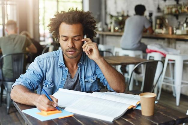 Innenporträt des attraktiven modischen afroamerikanischen universitätsabsolventen, der mit seinem forschungsleiter am smartphone spricht, während er am diplompapier arbeitet und am kaffeetisch sitzt
