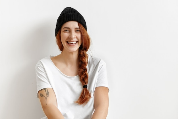 Innenporträt des attraktiven rothaarigen europäischen hipster-studentenmädchens, das weißes t-shirt trägt