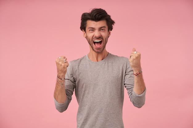 Innenporträt des aufgeregten gutaussehenden bärtigen mannes, der grauen pullover trägt, mit erhobenen fäusten steht und mit weit geöffnetem mund schaut