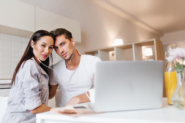 Innenporträt des erfreuten ehepaares, das wochenendmorgen zusammen verbringt und laptop verwendet