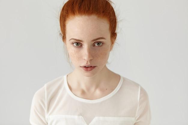 Innenporträt des ernsten niedlichen jungen rothaarigen weiblichen modells mit sommersprossen und grünen augen. hübsches mädchen mit ingwerhaarbrötchen, das weiße bluse trägt, die drinnen ruht
