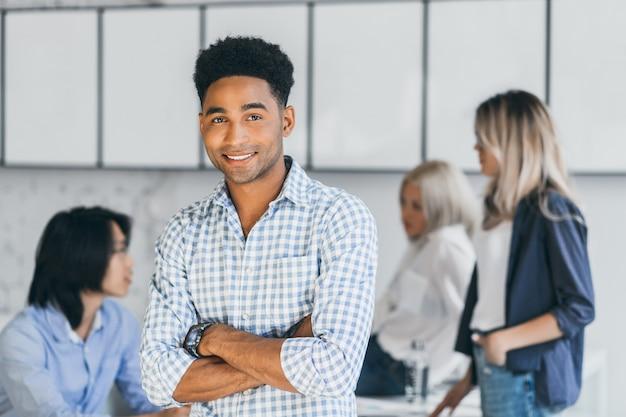 Innenporträt des frohen afrikanischen studenten im blauen hemd, das mit verschränkten armen steht, während seine universitätsfreunde neben ihm sprechen. glückseliger schwarzer, der zeit im büro mit kollegen verbringt.