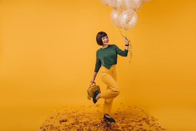 Innenporträt des geburtstagskindes, das auf einem bein aufwirft und lächelt. nette weiße frau im gelben hosen tanzen.