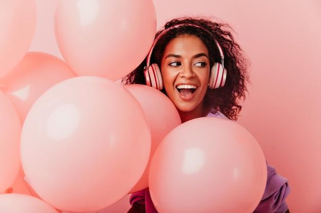Innenporträt des glückseligen geburtstagskindes, das positive gefühle auf pastell ausdrückt. lustige afrikanische frau in den großen kopfhörern, die mit vergnügen neben partyballons aufwerfen.