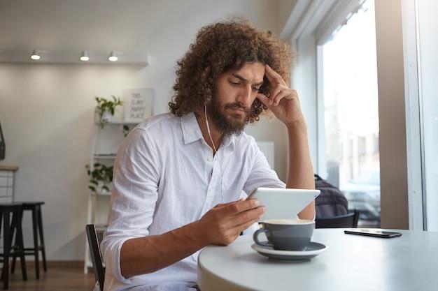 Innenporträt des hübschen jungen bärtigen mannes mit dem braunen lockigen haar, das nachrichten auf seinem tablett liest, im stadtcafé sitzt und eine tasse kaffee trinkt