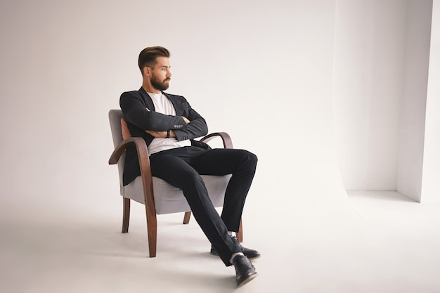 Innenporträt des hübschen jungen männlichen anwalts mit dickem bart und trendiger frisur, der bequem im sessel sitzt, arme auf der brust verschränkt hält und mit nachdenklichem nachdenklichem ausdruck wegschaut