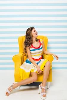 Innenporträt des inspirierten niedlichen mädchens, das sandalen mit hohen absätzen und gestreiftes buntes kleid trägt. anmutige junge frau mit gebräunter haut auf gelbem sessel, die in ihrem zimmer steht und lacht ..