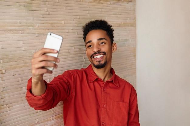 Innenporträt des jungen fröhlichen gutaussehenden kurzhaarigen dunkelhäutigen kerls, der breit lächelt, während er porträt von sich selbst macht, das auf hauptinnenraum steht