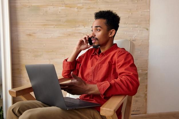 Innenporträt des jungen kurzhaarigen bärtigen kerls mit der dunklen haut, die telefongespräch beim sitzen vor dem fenster im stuhl, außerhalb des büros arbeitend hat