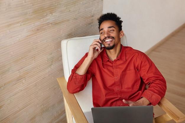 Innenporträt des jungen reizenden brünetten bärtigen mannes mit dunkler haut, die seinen kopf auf kopfstütze zurückwirft, während er im stuhl sitzt und während des telefongesprächs fröhlich lächelt