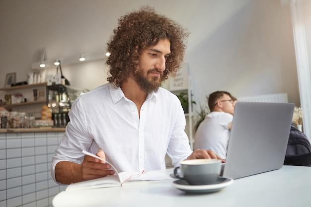 Innenporträt des jungen schönen geschäftsmannes, der neues projekt vorbereitet, das im öffentlichen raum unter verwendung von wi-fi und modernem laptop arbeitet und bildschirm mit zufriedenem gesicht betrachtet