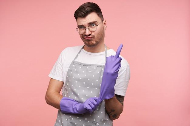 Innenporträt des jungen unzufriedenen kurzhaarigen brünetten mannes in den gläsern, die lila gummihandschuhe anziehen und mittelfinger lokalisiert auf rosa zeigen