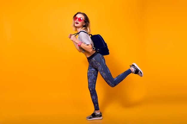 Innenporträt des lachenden mädchens, das mit muskeln auf gelbem hintergrund spielt. formschöne junge frau in leggings und grauem t-shirt, die flasche wasser hält und sport treibt.