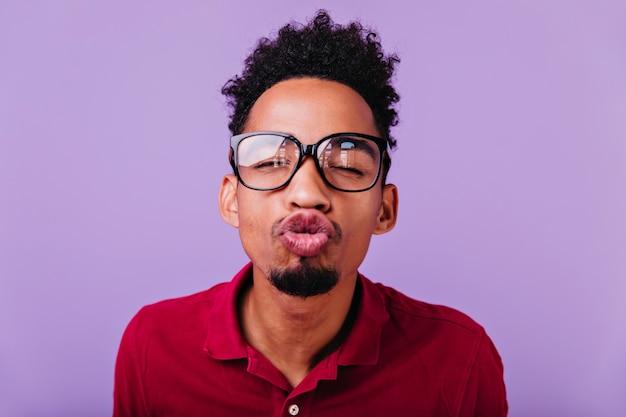 Innenporträt des lustigen afrikanischen mannes, der mit küssendem gesichtsausdruck aufwirft. nahaufnahmefoto des sorglosen brünetten jungen, der herumalbert.