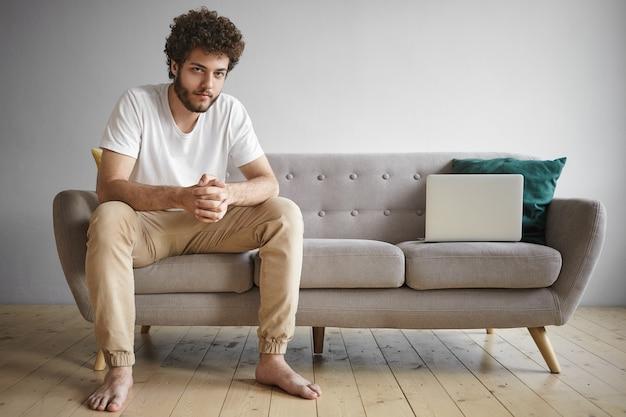 Innenporträt des modischen selbständigen jungen bärtigen mannes in der freizeitkleidung, die von zu hause aus arbeitet, mit wlan auf tragbarem elektronischem gerät, auf sofa im wohnzimmer mit generischem laptop sitzend