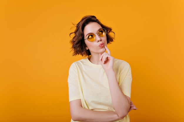 Innenporträt des nachdenklichen brünetten mädchens im hellgelben t-shirt. frohe kurzhaarige frau mit sonnenbrille, die aufschaut und über etwas nachdenkt.
