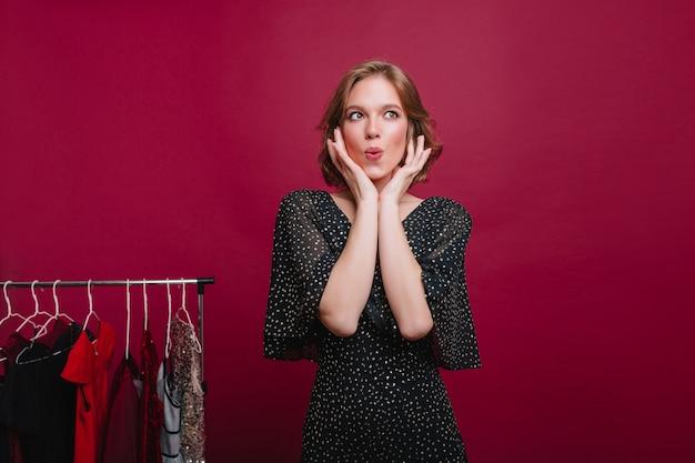 Innenporträt des nachdenklichen weiblichen shopaholic, der in der boutique aufwirft