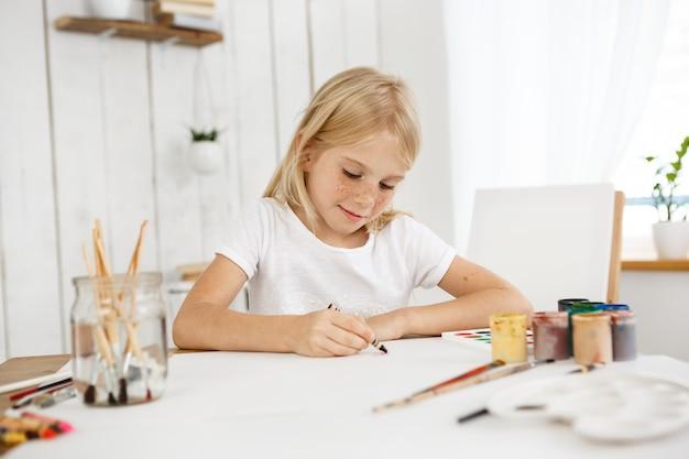 Innenporträt des niedlichen kleinen blonden mädchens mit sommersprossen, die mit wachsmalstiftfarbe auf dem blatt papier zeichnen