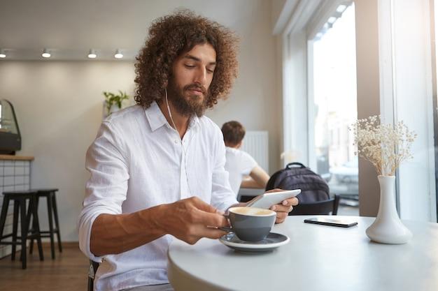 Innenporträt des reizenden lockigen dunkelhaarigen kerls, der tasse kaffee trinken wird, während musik mit kopfhörern auf seinem tablett hört, das weißes hemd trägt