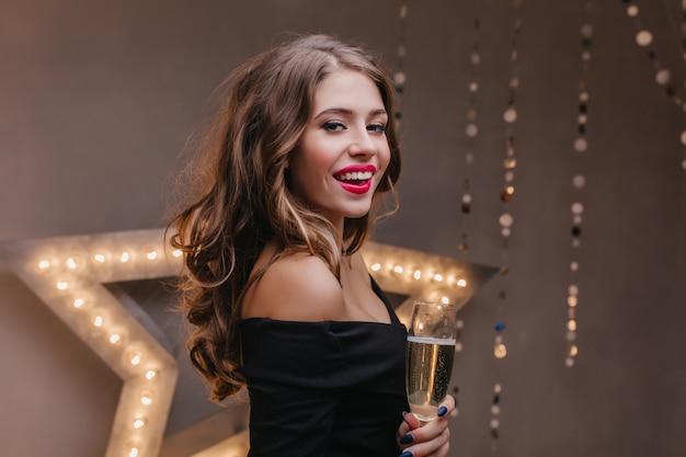 Innenporträt des reizenden weiblichen modells mit roten lippen, die wein nahe leuchtendem stern schmecken. atemberaubende junge frau im schwarzen weinglas mit aufrichtigem lächeln.