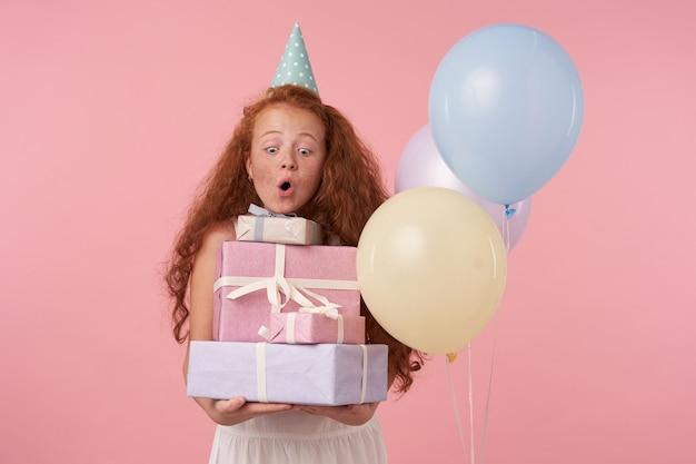Innenporträt des rothaarigen weiblichen kindes in der festlichen kleidung und in der geburtstagskappe, die auf rosa mit geschenkboxen in den händen aufwirft, aufgeregt und überrascht ist, geburtstagsgeschenke zu erhalten