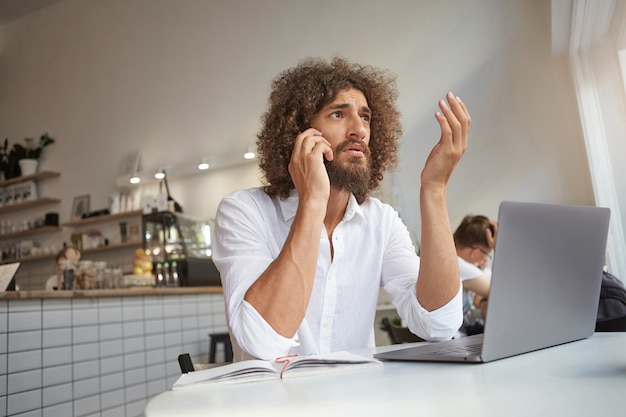 Innenporträt des schönen jungen freiberuflers mit bart, der entfernt an öffentlichem ort arbeitet und mit der hand gestikuliert, während ernsthaftes gespräch am telefon geführt wird