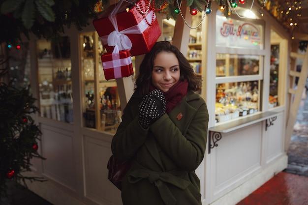 Innenporträt des schönen mädchens in der roten winterjacke, die schnee auf weihnachtsmarkt durchbrennt