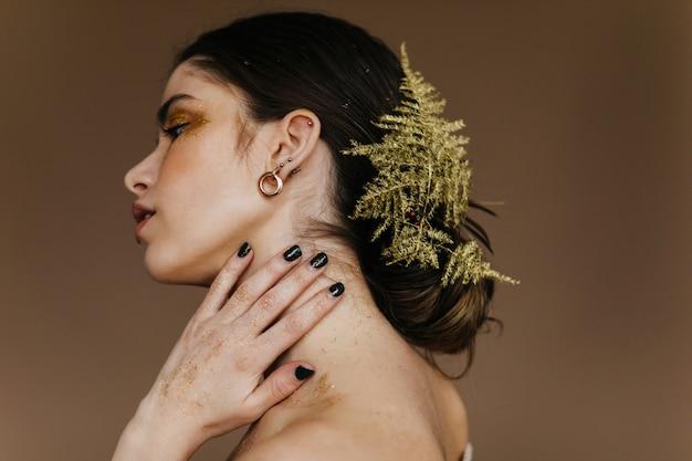 Innenporträt des schönen mädchens mit pflanze im schwarzen haar. stilvolle blithesome dame, die auf brauner wand aufwirft.