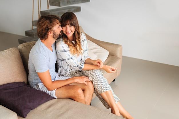 Innenporträt des verliebten paares, das auf gemütlichem sofa sitzt