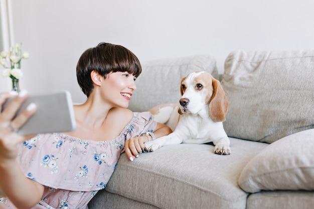 Innenporträt des wunderbaren dunkelhaarigen mädchens, das selfie mit beagle-hund macht, der auf sofa liegt