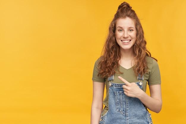 Innenporträt einer jungen ingwerfrau, trägt blaue jeans-overalls und grünes t-shirt, zeigt im kopierraum mit finger lächelt breit mit zufriedenem gesichtsausdruck. isoliert über gelber wand