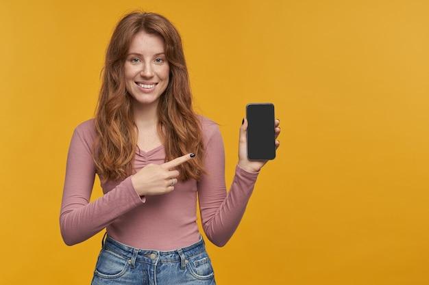 Innenporträt einer jungen ingwerfrau, zeigen sie mit einem finger auf die leere anzeige ihres telefons mit erstauntem, schockiertem gesichtsausdruck