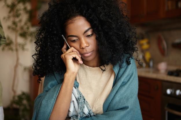 Innenporträt einer traurigen, unglücklichen, jungen, dunkelhäutigen hausfrau, die vor einem finanziellen problem steht und viele schulden hat, die auf dem smartphone mit dem wohnungsdienst sprechen und darum bitten, das benzin in ihrer wohnung nicht abzuschalten